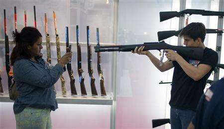 A woman uses a smart phone to photograph a young man holding a shotgun at an exhibit booth at the George R. Brown convention center, the site for the National Rifle Association's (NRA) annual meeting in Houston, Texas May 5, 2013. REUTERS/Adrees Latif