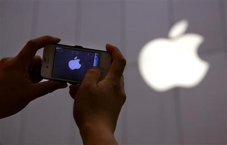 A man shows a photograph he took on his iPhone of an Apple store in Beijing June 6, 2012 file photo. REUTERS/David Gray