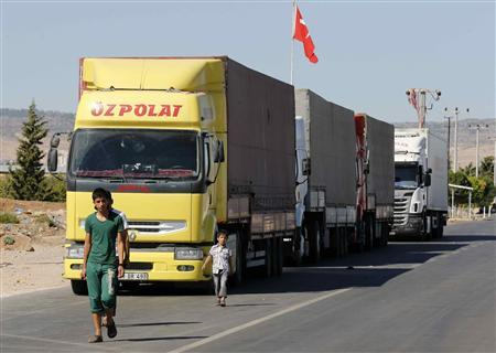 Locals walk past trucks lined up at the Oncupinar border crossing on the Turkish-Syrian border in the southeastern city of Kilis September 5, 2013. Every day, hundreds of trucks piled high with goods ranging from cooking oil to cement and nappies form queues stretching for miles at Oncupinar, now a bustling hub for trade with Syria. REUTERS/Umit Bektas