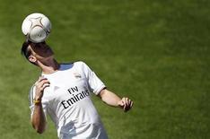 """O jogador natural de Wales Gareth Bale cabeceia a bola durante sua apresentação ao Real Madrid, no estádio Santiago Bernabéu, em Madri. Gareth Bale considerou """"no mínimo estressante"""" a arrastada negociação que levou à transferência do Tottenham Hotspur para o Real Madrid pela quantia recorde de 100 milhões de euros (132 milhões de dólares). 2/09/2013. REUTERS/Sergio Perez"""