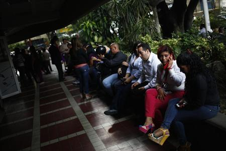 People sit outside a shopping mall during a massive blackout in Caracas September 3, 2013. REUTERS/Jorge Silva