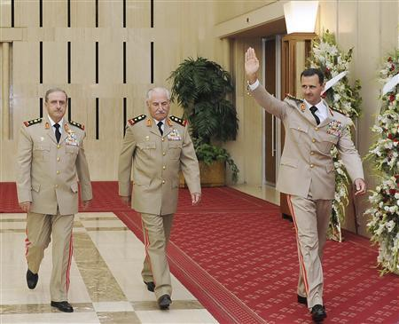 Syria's President Bashar al-Assad (R) waves as he arrives with Syrian Defense Minister General Ali Habib (C) and Chief of Staff General Dawoud Rajha to attend a dinner to honour army officers on the 65th Army Foundation anniversary in Damascus in this August 1, 2010 file photo. REUTERS/SANA/Handout