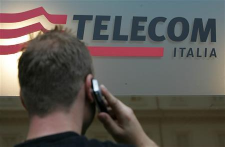 A man uses a mobile phone in front of a Telecom Italia shop in downtown Rome September 14, 2006. REUTERS/Dario Pignatelli
