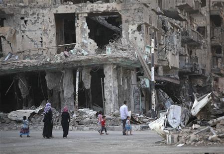 People walk along a damaged street filled with debris in Deir al-Zor September 4, 2013. Picture taken September 4, 2013. REUTERS/Khalil Ashawi