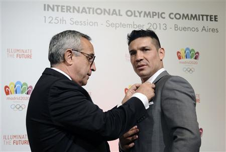 Alejandro Blanco (L), President of Madrid 2020 Committee and the Spanish Olympic Committee, gives a pin to World Boxing Council (WBC) middleweight champion Sergio Martinez of Argentina after a news conference in Buenos Aires September 5, 2013. REUTERS/Charly Diaz Azcue