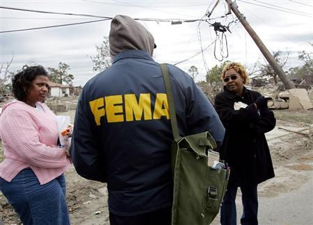 Lower Ninth Ward residents Eileen Lange (L) and Janet Aubert (R) question a representative from the Federal Emergency Management Agency (FEMA) in New Orleans December 2, 2005. Residents of the Lower Ninth Ward, one of the hardest hit areas of Hurricanes Katrina and Rita, were permitted to visit their homes and recover belongings for the first time on December 1. REUTERS/Lee Celano - RTR19Z7T