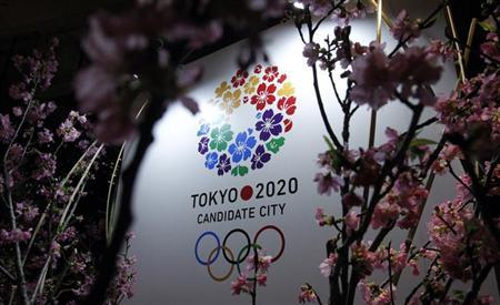 Tokyo 2020 Olympic bid logo is seen through cherry blossom at a hotel in Tokyo, March 7, 2013. REUTERS/Yuya Shino