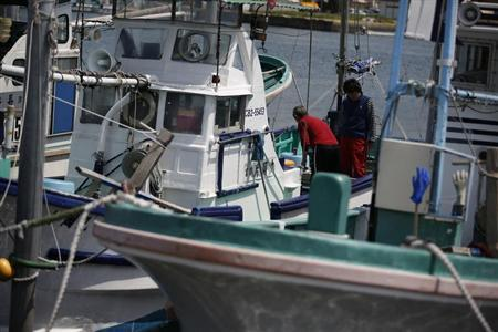Fishermen work on a moored fishing boat at a fishery harbour in Futtsu, east of Tokyo April 25, 2013. REUTERS/Issei Kato