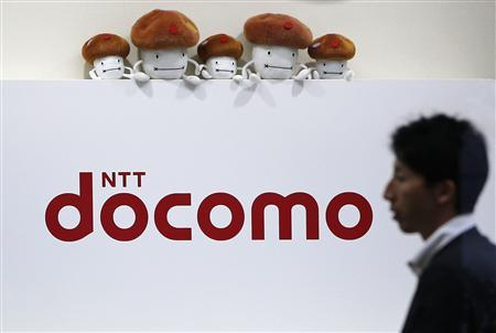 A man walks past the logo of Japan's biggest mobile phone operator NTT Docomo at its shop in Tokyo in this July 3, 2013 file photograph. REUTERS/Issei Kato/Files