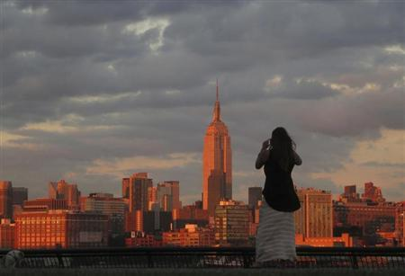 A woman stops to photograph the skyline of New York across from the Empire State Building as she walks in a park along the Hudson River in Hoboken, New Jersey, September 3, 2013. REUTERS/Gary Hershorn