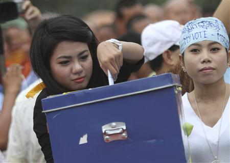 A youth volunteer of the Cambodian National Rescue Party (CNRP) slots in money into a box during a rehearsal of a demonstration ahead of the planned September 8 mass protests, at the Freedom Park in Phnom Penh September 4, 2013. REUTERS/Samrang Pring