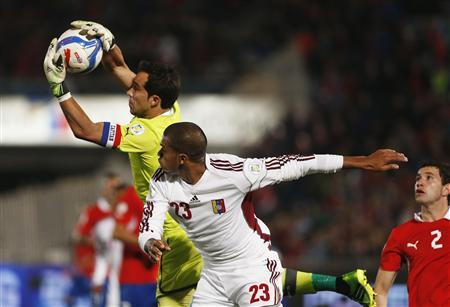 Chile's goalkeeper Claudio Bravo (L) makes a save under pressure from Venezuela's Jose Salomon Rondon (R) during a 2014 World Cup qualifying soccer match in Santiago, September 6, 2013. REUTERS/Ivan Alvarado