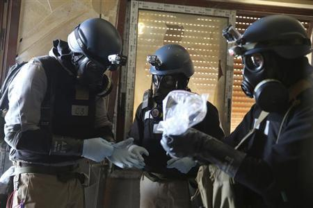A U.N. chemical weapons expert, wearing a gas mask, holds a plastic bag containing samples from one of the sites of an alleged chemical weapons attack in the Ain Tarma neighbourhood of Damascus August 29, 2013. REUTERS/Mohamed Abdullah