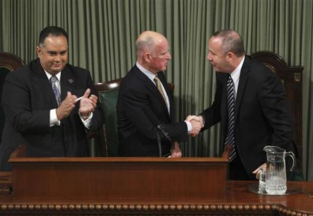 California Governor Jerry Brown (C) is congratulated by Senate President pro Tempore Darrell Steinberg (R) as Assembly Speaker John Perez (L) looks on, after he delivered his State of the State address in the Assembly Chambers at the State Capitol in Sacramento, California, January 18, 2012. REUTERS/Rich Pedroncelli/Pool