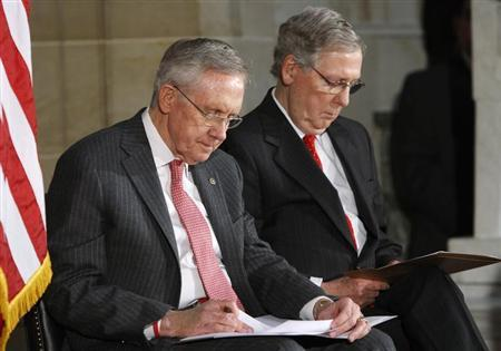 U.S. Senate Majority Leader Harry Reid (D-NV) (L) and Senate Minority Leader Mitch McConnell (R-KY) (R) look at their notes during a ceremony for the 50th anniversary of the March on Washington for Jobs and Freedom at the U.S. Capitol in Washington, July 31, 2013. REUTERS/Jonathan Ernst