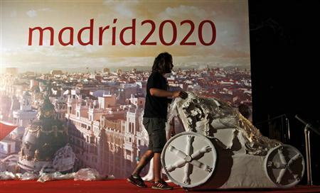 A worker wheels away a replica of the Cibeles fountain in front of an advertising backdrop for the Madrid candidacy for the 2020 Summer Olympic Games after the announcement that Madrid has been eliminated from the International Olympic Committee's voting process to select the host city, in Madrid September 7, 2013. REUTERS/Paul Hanna