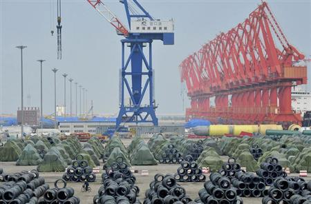 A worker rides his bicycle past piles of steel coils for export at a port in Yingkou, Liaoning province August 9, 2013. REUTERS/Stringer