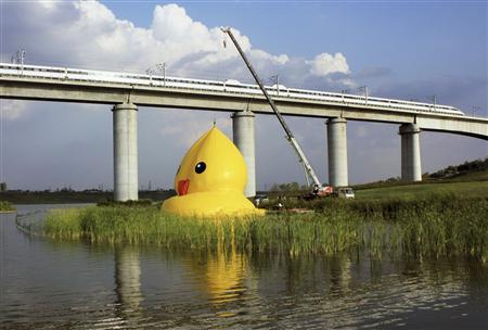 An inflatable Rubber Duck by Dutch conceptual artist Florentijn Hofman, is being set up next to a high-speed railway viaduct bridge on a lake at the venue of the 9th China International Garden Expo in Beijing, September 5, 2013. The 18-metre-high inflatable sculpture, which made its first public appearance in the city on Friday, will be shown at the expo until September 23, after which it will be transported to the Summer Palace to display for another month, local media reported. Picture taken September 5, 2013. REUTERS/Stringer