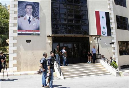 Journalists and security personnel stand in front of Yousef al-Azma military hospital during a visit by team of United Nations chemical weapons experts in Damascus August 30, 2013. REUTERS/Khaled al-Hariri