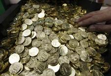 Десятирублевые монеты на Санкт-Петербургском монетном дворе 9 февраля 2010 года. Рубль в небольшом минусе утром понедельника - позитивный внешний фон перебивается спросом на валюту, подешевевшую после трудовой статистики США; в ближайшие дни динамика будет определяться во многом спекуляциями вокруг возможных шагов ФРС по сокращению стимулирующих программ. REUTERS/Alexander Demianchuk