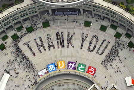 An aerial view shows people sitting in formation to the words ''thank you'' and displaying signs that collectively read ''Arigato'' (Thank You) during an event celebrating Tokyo being chosen to host the 2020 Olympic Games, at Tokyo Metropolitan Government Building in Tokyo, in this photo taken by Kyodo September 8, 2013. REUTERS/Kyodo