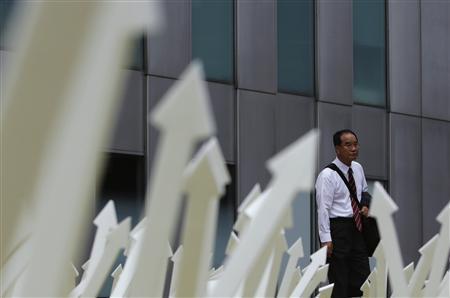 A man walks past an artwork displayed in Tokyo's business district September 8, 2013. REUTERS/Yuya Shino