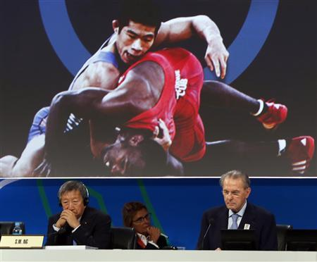 President of the International Olympic Committee (IOC) Jacques Rogge (R) listens to the presentation of wrestling to be included as an Olympic sport next to committee member Ng Ser Miang in Buenos Aires September 8, 2013. REUTERS/Marcos Brindicci