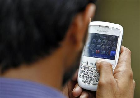 A man checks his mobile phone near a marketplace in New Delhi June 18, 2013. REUTERS/Anindito Mukherjee/Files
