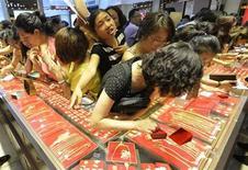 Покупатели в ювелирном магазине в Тайюане в провинции Шаньси 6 июля 2013 года. Цены на золото стабилизировались после роста в пятницу, когда слабые данные о занятости США вызвали ожидания, что ФРС в ближайшее время продолжит стимулирование экономики. REUTERS/Jon Woo