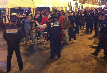 A photo, taken with a mobile phone, shows an injured English soccer fan lying on a stretcher and surrounded by medical personnel, police and other people in central Kiev September 8, 2013. REUTERS/Alexander Fedchenko/Komsomolskaya Pravda in Ukraine