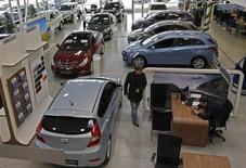 Мужчина проходит мимо выставленных на продажу автомобилей в салоне Hyundai в Санкт-Петербурге 15 января 2013 года. Российский авторынок сократился в августе 2013 года на 10 процентов в годовом исчислении до 231.915 штук, сообщила в понедельник Ассоциация европейского бизнеса (АЕБ). REUTERS/Alexander Demianchuk