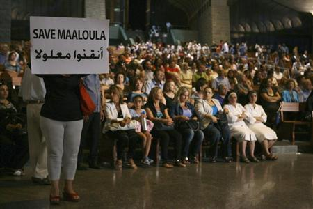 A Syrian woman holds a banner for saving Maaloula while Lebanese and Syrian Christian Maronites pray for peace in Syria, in Harisa, Jounieh September 7, 2013. REUTERS/Hasan Shaaban