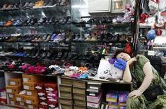 Женщина дремлет в магазине обуви в Пекине 3 сентября 2013 года. Рост мировой торговли, как ожидается, составит 2,5 процента в 2013 и 4,5 процента в 2014 году, сообщил в понедельник новый глава Всемирной торговой организации (ВТО) Роберту Азеведу, пересмотрев в сторону снижения предыдущий прогноз на уровне 3,3 и 5 процентов, соответственно. REUTERS/Kim Kyung-Hoon