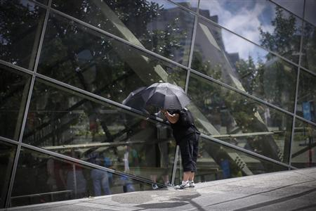 A visitor to the 911 Memorial plaza peers through glass windows into the 911 Memorial Museum, which is under construction, at the World Trade Center site in New York, July 2, 2013. REUTERS/Mike Segar