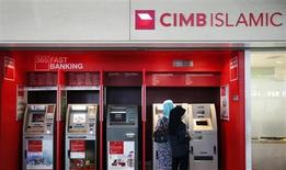 People withdraw cash from an automatic teller machine at a CIMB Islamic branch in Sepang outside Kuala Lumpur August 26, 2013. REUTERS/Bazuki Muhammad