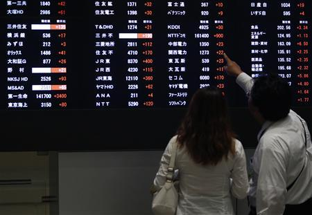 A visitor points at a stock price displayed on an electronic board at the Tokyo Stock Exchange in Tokyo September 9, 2013. REUTERS/Yuya Shino