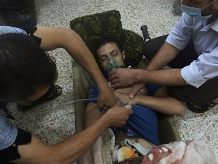 A man, affected by what activists say is nerve gas, breathes through an oxygen mask in the Damascus suburbs of Jesreen August 21, 2013. REUTERS/Ammar Dar