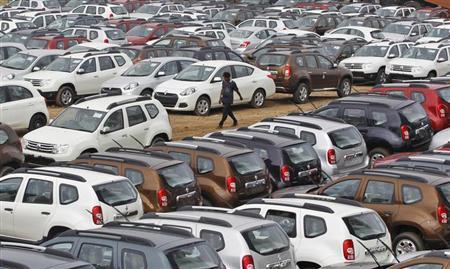 A worker walks past parked Renault cars at its stockyard on the outskirts of Ahmedabad June 11, 2013. REUTERS/Amit Dave/Files
