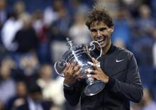 Теннисист Рафаэль Надаль с трофеем, завоеванным на Открытом чемпионате США по теннису в Нью-Йорке 9 сентября 2013 года. Рафаэль Надаль во второй раз в карьере выиграл Открытый чемпионат США по теннису, в понедельник вечером одолев серба Новака Джоковича. REUTERS/Eduardo Munoz