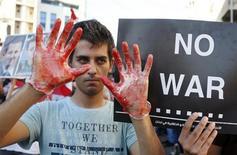 """Участник демонстрации против возможного удара по Сирии на фоне плаката с надписью """"Нет войне"""" у посольства США в Ливане 6 сентября 2013 года. Президент США Барак Обама увидел возможность прорыва в кризисной ситуации вокруг Сирии после того, как Россия внесла предложение о передаче Дамаском химического оружия под международный контроль для его последующего уничтожения, что могло бы предотвратить удар США по этому ближневосточному государству. REUTERS/Mohamed Azakir"""
