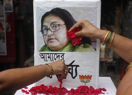 Supporters of India's main opposition Hindu nationalist Bharatiya Janata Party (BJP) women's wing, scatter rose petals in front of a portrait of an Indian author Sushmita Banerjee, in Kolkata September 7, 2013. REUTERS/Rupak De Chowdhuri