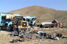 Бульдозер расчищает место автокатастрофы в Турции 18 августа 2006 года. По меньшей мере 44 человека погибли и 39 получили травмы в результате столкновения двух пассажирских автобусов близ Тегерана, сообщили иранские СМИ во вторник. REUTERS/Anatolian News Agency