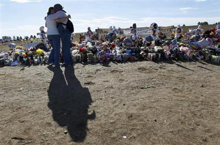 A couple hug early on Sunday morning in front of 12 white crosses at a memorial to those killed in the July 20 theater shootings in Aurora, Colorado July 29, 2012. REUTERS/Rick Wilking