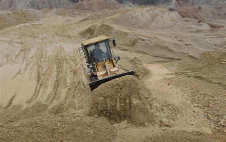 A labourer operates a bulldozer at a site of a rare earth metals mine at Nancheng county, Jiangxi province March 14, 2012. REUTERS/Stringer