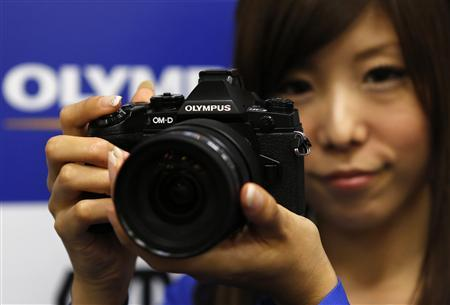 A model poses with Olympus Corp's new OM-D E-M1 digital camera during its unveiling in Tokyo September 10, 2013. REUTERS/Toru Hanai