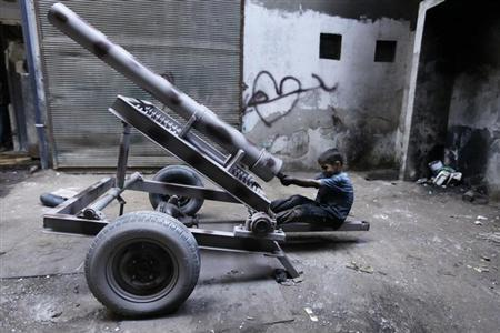 Issa, 10 years old, fixes a mortar launcher in a weapons factory of the Free Syrian Army in Aleppo, September 7, 2013. REUTERS/Hamid Khatib