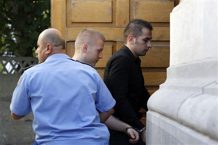 Eugen Darie (C) and Alexandru Bitu (R), suspects charged in the theft of seven paintings from a Dutch museum, arrive handcuffed and escorted by police for their trial at a court building in Bucharest September 10, 2013. REUTERS/Bogdan Cristel