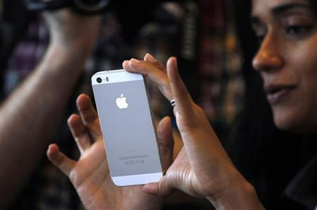 A woman tries the silver colored version of the new iPhone 5S after Apple Inc's media event in Cupertino, California September 10, 2013. REUTERS/Stephen Lam