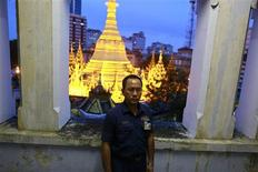Toe Aung, deputy head of urban planning, poses for a photo at the Yangon City hall, with the lit Sule Pagoda seen behind him, in Yangon, September 5, 2013. REUTERS/Soe Zeya Tun