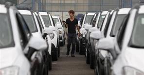 A worker checks cars made by GM Korea in a yard of GM Korea's Bupyeong plant before they are transported to a port for export, in Incheon, west of Seoul August 9, 2013. REUTERS/Lee Jae-Won